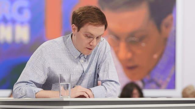 Mannin hellblauem Hemd sitzt an einem tisch und liest von einem Blatt.