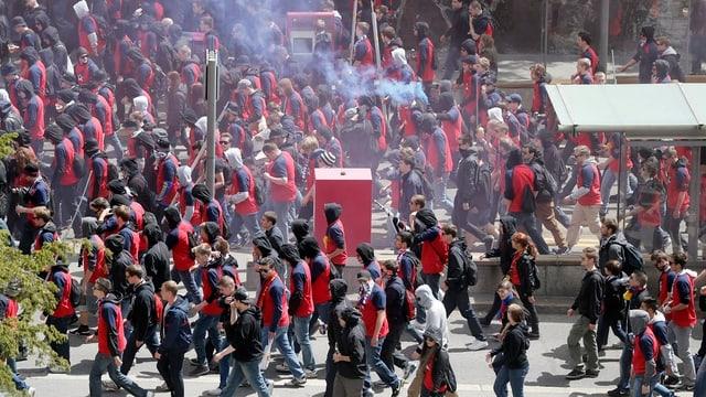 Eine Menschenmenge mit rot-blauen Trikots und Kapuzen.