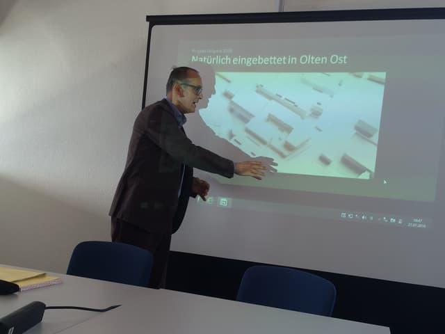 Mann präsentiert vor Leinwand das Projekt