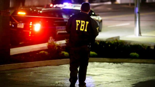 FBI-Beamter vor einem erleuchteten Fahrzeug.