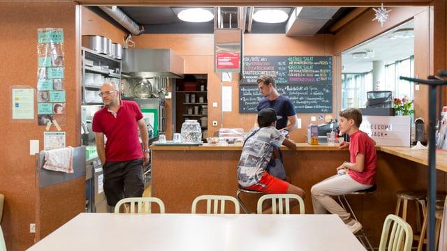 Zwei Jugendliche und zwei Helfer an der Bar des Jugendzentrums.