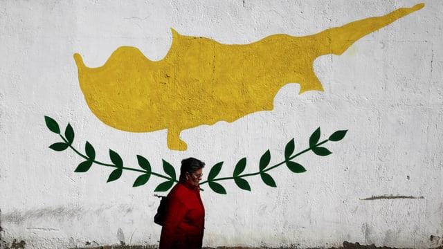 Frau spaziert vor einer Fassade durch, auf der die zypriotische Flagge abgebildet ist