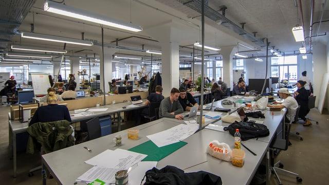 Blick in einen grossen Raum mit langen Tischreihen. Schüler sitzen an den Tischen. Es sieht sehr lebendig aus.