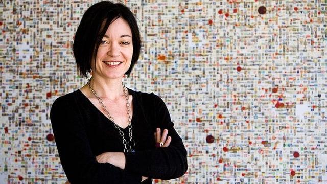 Porträt von Sue Gardner in Schwarz vor einer Wand mit feinen, bunten Punkten und Quadraten.