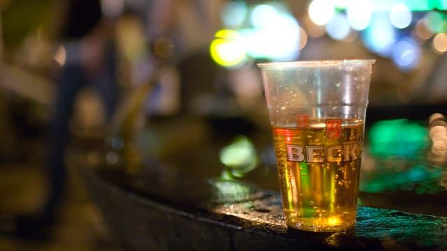 Ein Becher Bier steht auf einem Brunnenrand, im Hintergrund verschwommene Gestalten Nachtlichter