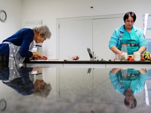 Diese zwei Frauen arbeiten selbständig an der Pizza.