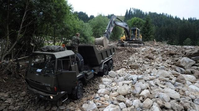 Ein Armee Lastwagen und ein Bagger bei Aufräumarbeiten nach einem Unwetter.
