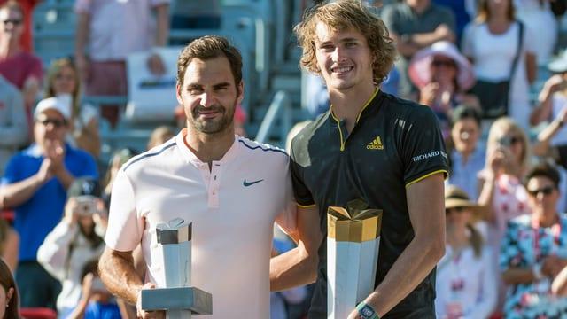 Zverev und Federer sind stehen mit einem Pokal da und lächeln in die Kamera