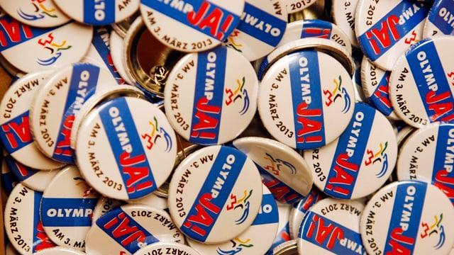 Ansteckbuttons mit dem Aufdruck OlympJA! für die Abstimmung vom 3. März 2013.
