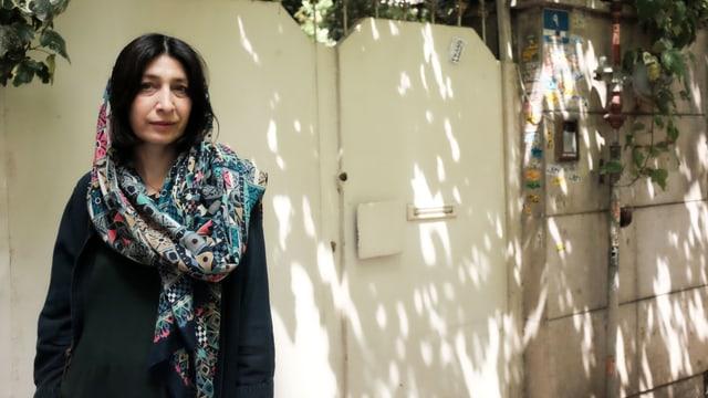 Eine Frau steht vor einer Türe