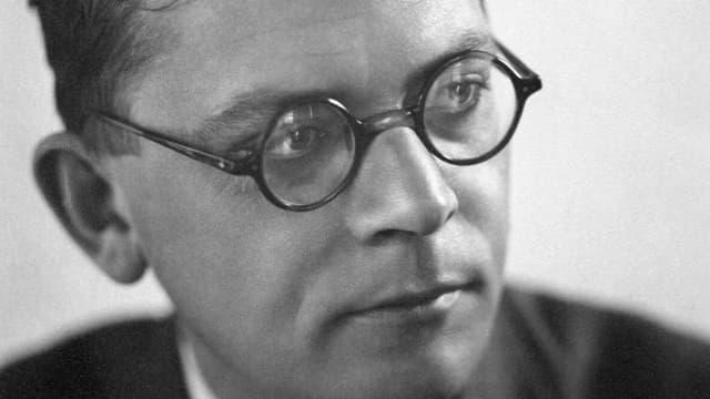 Ein Mann mit Brille schaut zur Seite.