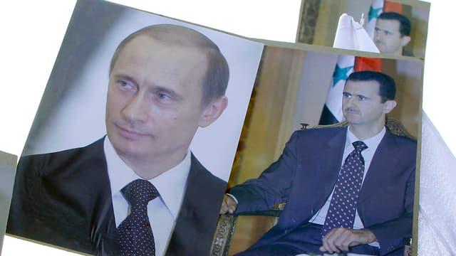 Demonstranten tragen Plakate mit den Porträts von Putin und Assad