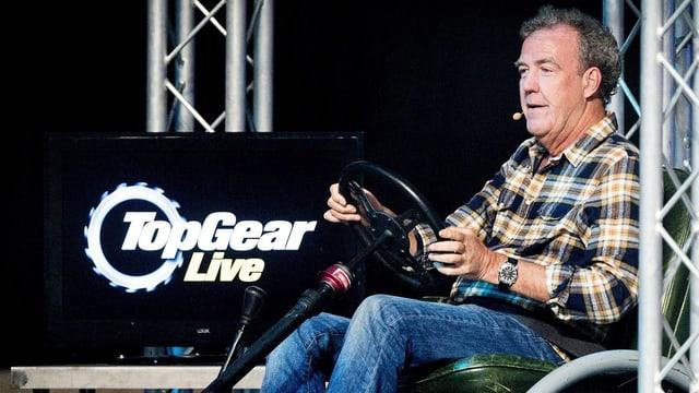 Jeremy Clarkson sitzt auf einem Stuhl, vor ihm ein Lenkrad.