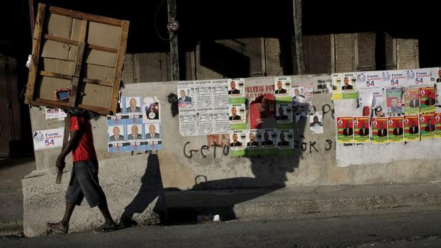 Wahlplakate diverser Kandidaten an einer Mauer.