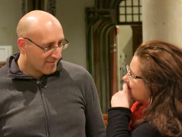 Einer der Dirigenten spricht mit einer Frau mit Brille und langen, braunen Haaren.