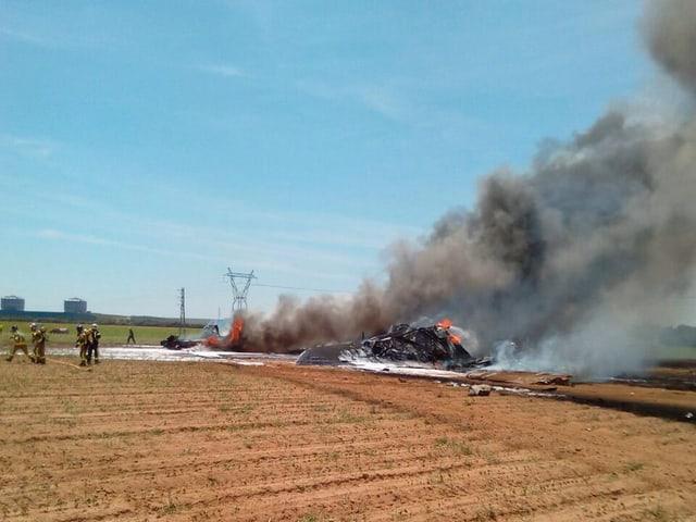 Brennende Flugzeug-Trümmer auf einem Feld.