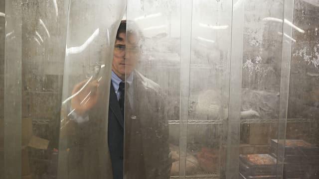 Ein Mann öffnet einen Plastikvorhang.