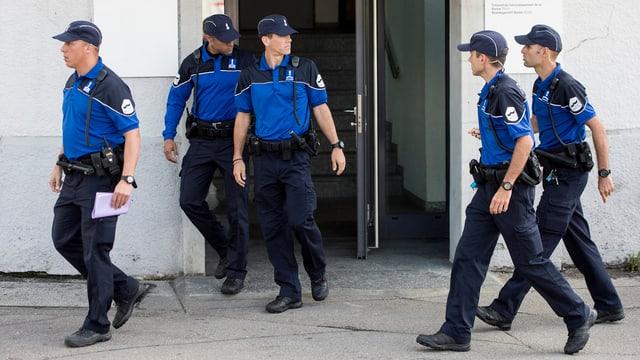 Uniformierte Polizisten laufen aus einem Gebäude.