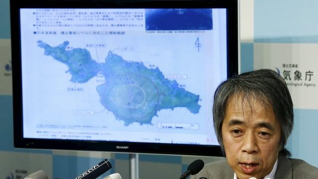 Ein Mann vor einem Bildschirm mit einer Insel-Karte