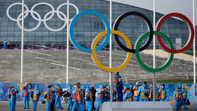 Olympische Ringe vor einem Sportstadion.