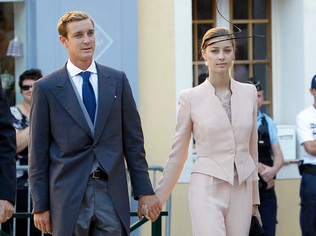 Pierre Casiraghi im grauen Frak. Hand in Hand mit seiner Verlobten Beatrice welche in altrosafarbenen Anzug mit passendem Hut trägt.