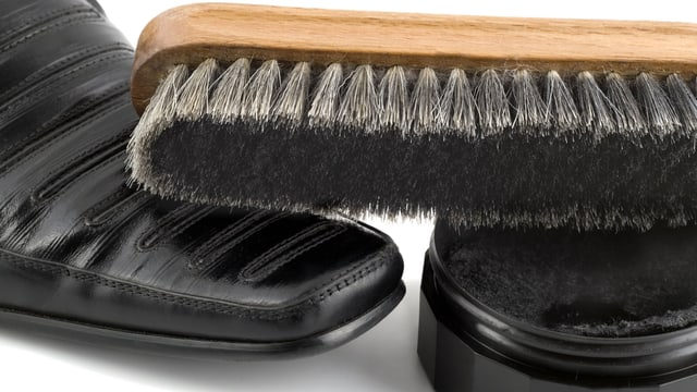 Schwarzer Herrenschuh, eine Dose Schuhcreme und eine Schuhbürste.
