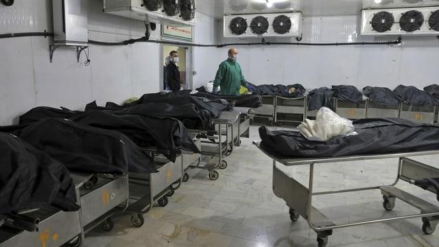 Leichenhalle mit Säcken auf Bahren.