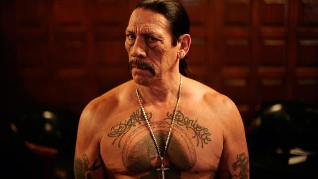 Trejo mit nacktem Oberkörper und grossem Tattoo auf der Brust.