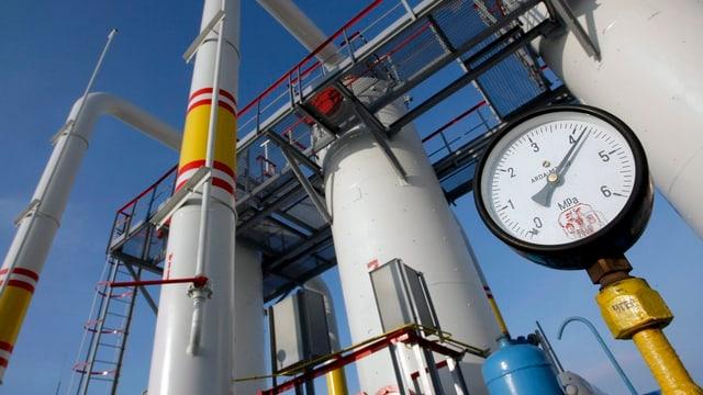 Druckmesser einer Gasleitung im Hintergrund Silos