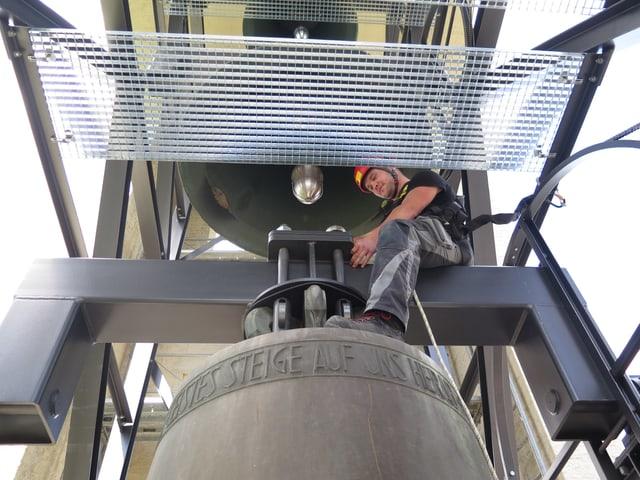 Mann sitzt auf Geländer, darunter Glocke.