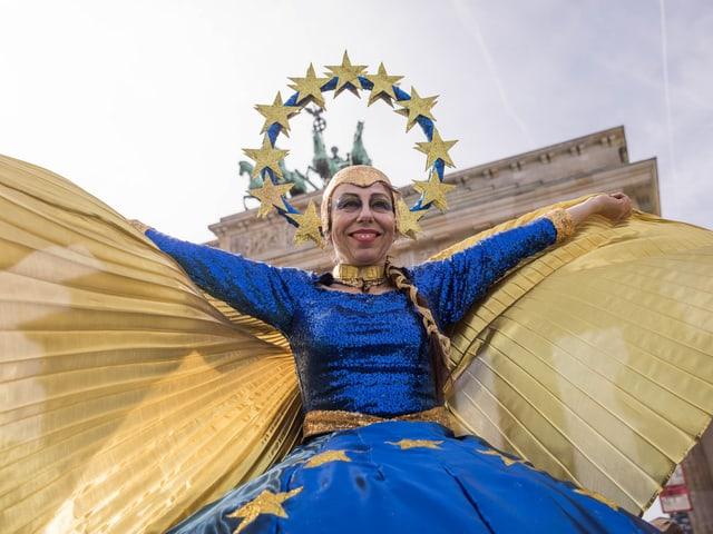 Eine als Europa verkleidete Frau vor dem Brandenburger Tor.