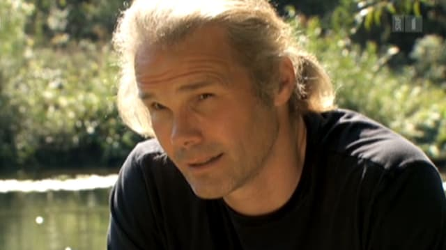Christopher Exley bei einem Interview an einem See.