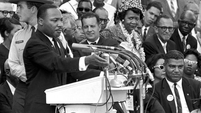 Ein Mann steht am Rednerpult vor einer Menschenmenge