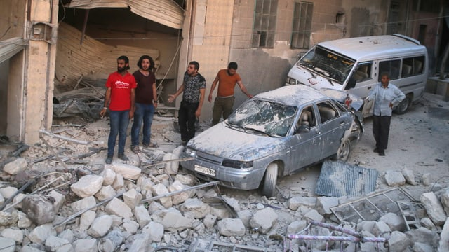 Männer begutachten Schäden an zwei Autos in einem Quartier von Aleppo nach einem Luftangriff auf die Rebellen, auf der Strasse liegen Gesteinstrümmer
