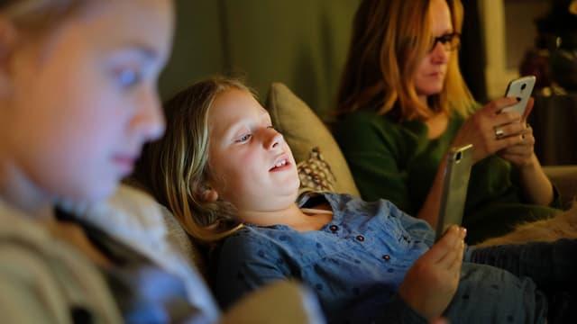 Eine Frau und zwei Mädchen sitzen nebeneinander, jede mit dem Smartphone in der Hand