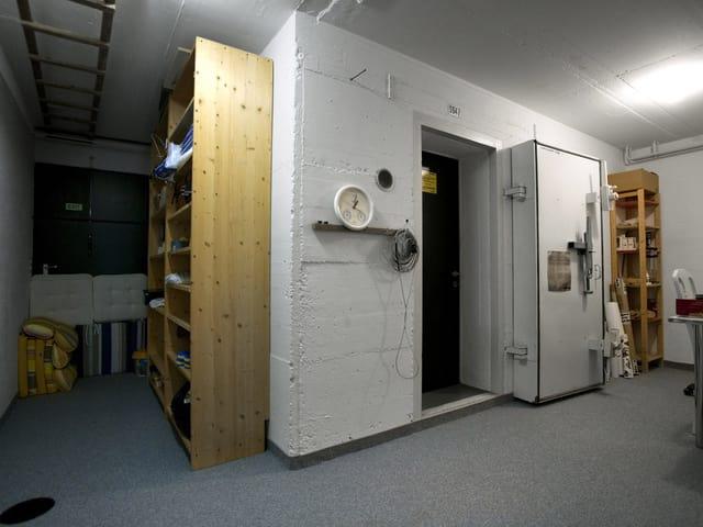 Zu sehen ist die gepanzerte Eingangstür zu einem Schutzraum. Daneben ein Keller-Regal und einige eingelagerte Kissen für Gartenmöbel.