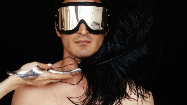 Ein Mann mit reflektierender Brille wird mit einer schwarzen Feder gestreichelt.