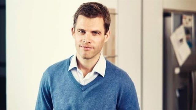 Ein junger Mann mit kurzen braunen Haaren, mit blauem Pullover und weissem Hemd darunter schaut in die Kamera