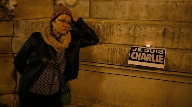 Frau an Wand lehnend, Daneben ein Plakat darauf steht: «Je suis Charlie»