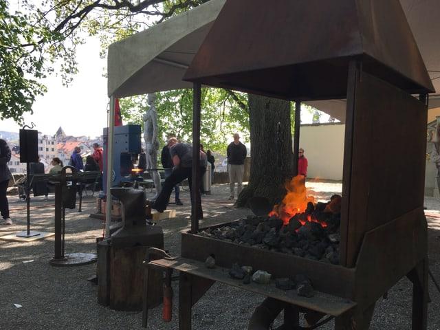 Ein Feuer glüht in einer Art grossen Grill.