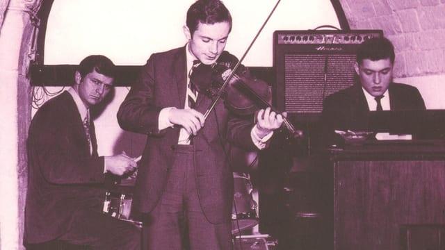 Schwarzweiss Foto. Drei Musiker spielen auf einer winzig kleinen Bühne. Vorne der Musiker Jean-Luc Ponty mit der Geige, hinten der Schlagzeugspieler Daniel Humair und daneben Eddy Louis an der Orgel.