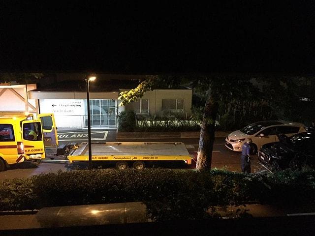 Die Polizei transportiert mit einem gelben Abschleppwagen ein schwarzes Auto ab. Es ist Nacht.