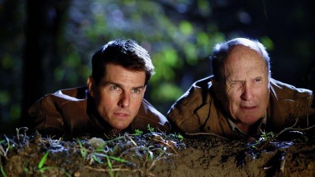 Zwei Männer gehen hinter einem Hügel auf Deckung.