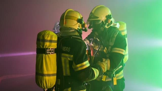 Zwei Feuerwehrleute mit Atomschutzanzügen