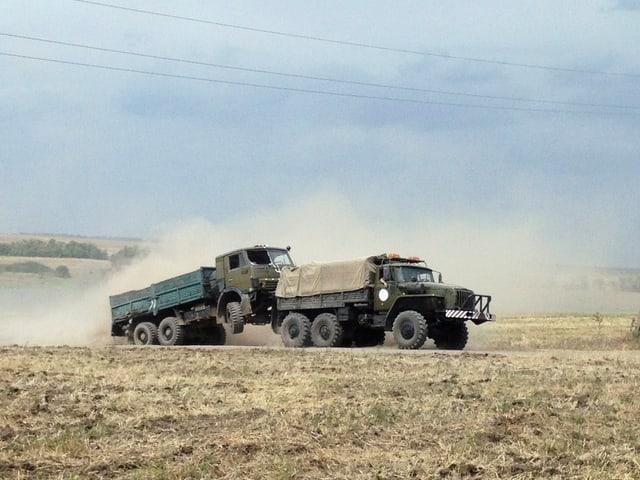 Ein Militärlastwagen schleppt einen zweiten ab