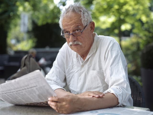Hansjörg Schneider sitzt an einem Tisch in einem Garetn und liest Zeitung.