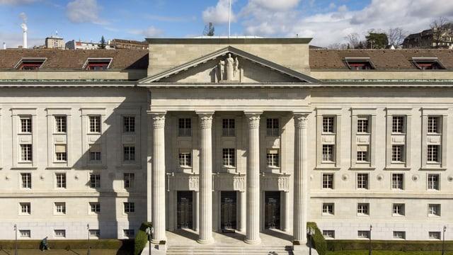 Ein Gebäude von aussen. Graue Fassade, vier grosse Säulen prägen den Eingang.