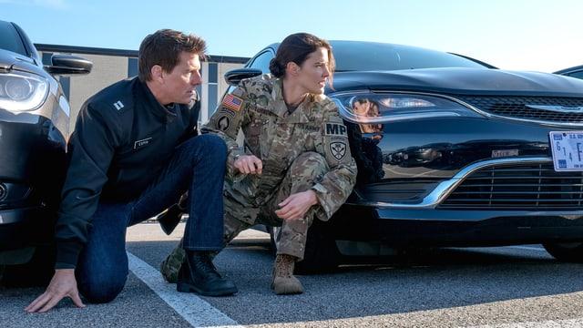 Tom Cruise und Cobie Smulders verstecken sich hinter einem Auto.