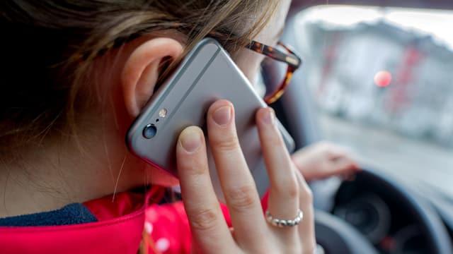 Frau am Telefonieren und Autofahren