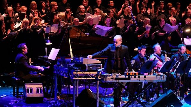 Ein Mann steht am Mischpult auf einer Bühne, eine Big Band ist im Hintergrund.